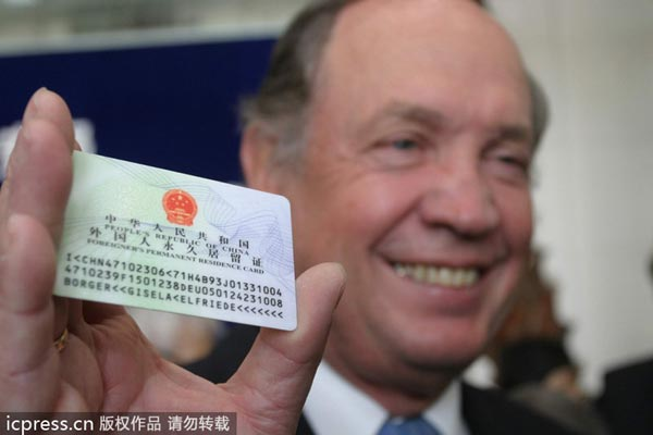 An expat poses for photos with his Chinese permanent residence card in this file photo. [Photo/IC