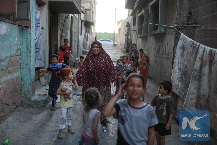 Hayat al-Hessi, 60, play with her grandchildren and her neighbors children in front of her small rundown house in the overcrowded Shati refugee camp in Gaza city. (Xinhua Photo)