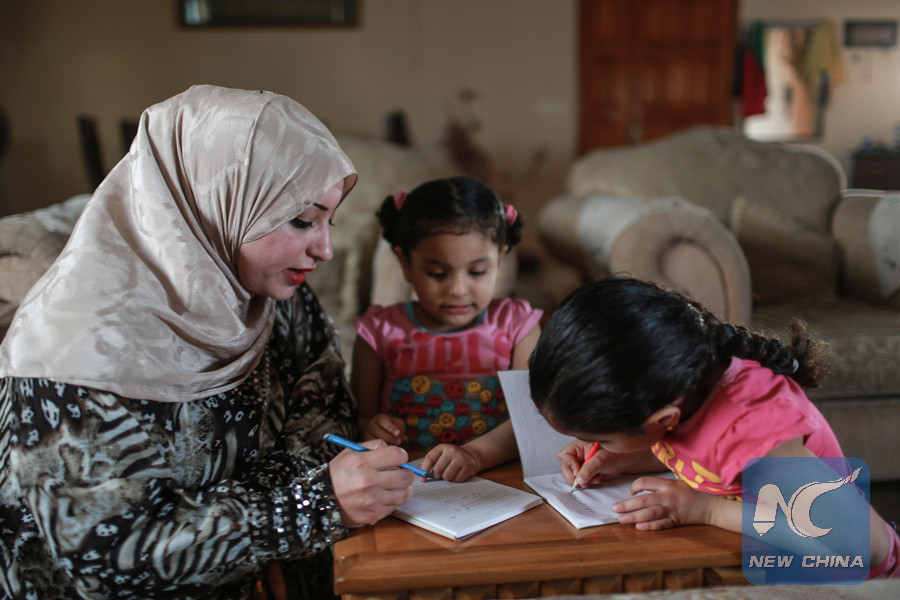 Rawan al-Katary, 29, helps her two daughters in doing their homework inside their house in Gaza city. (Xinhua Photo)